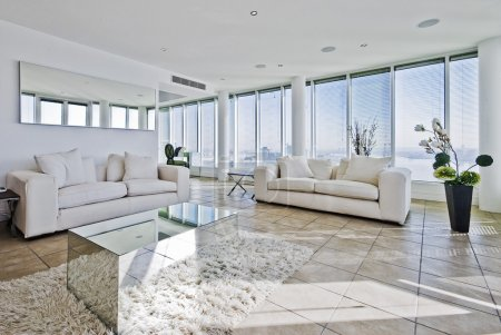 Photo for Spacious penthouse living room with floor to ceiling windows and modern furniture - Royalty Free Image