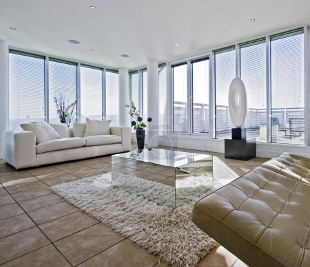 Massive luxury living room with chunky white fabric sofas and floor to ceiling windows