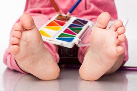 Baby's feet with paint and pencils