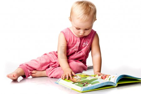 Beautiful baby girl lying reading a book
