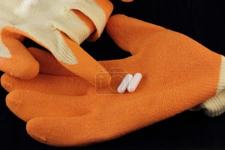 L - carnitine capsules placed on working gloves