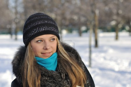 A beautiful girl walks in the park in winter. Smile