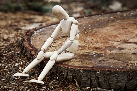 Photo for A wooden model sitting on the stump - Royalty Free Image