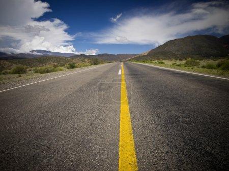 Photo pour Une route désertique par les montagnes entourée d'une nature colorée . - image libre de droit