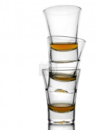 Photo for A pile of three almost empty shots of whiskey on white background with reflex. - Royalty Free Image