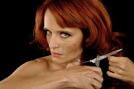 Photo pour Belle image d'une femme coupant ses propres cheveux - image libre de droit