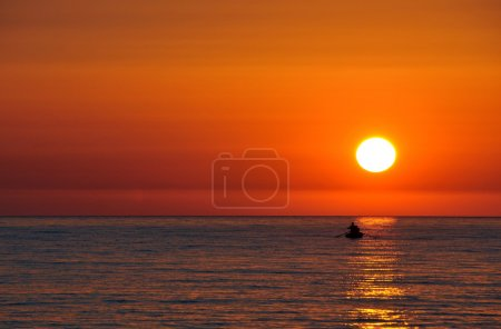 Photo for Silhouette of small boat against beautiful sunset - Royalty Free Image