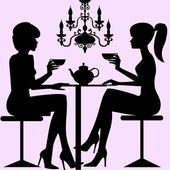 Silhouettes of two women sitting down talking and drinking tee or coffe background with old chandelier