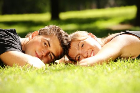 Photo for Young couple lying in the park and smiling - Royalty Free Image