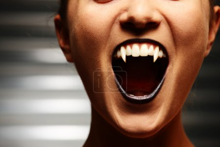 Close up of a vampire woman's mouth over dark back...