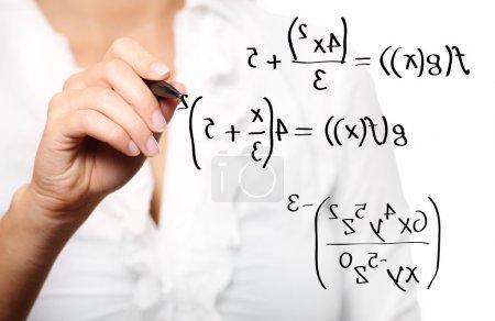Photo pour Une photo d'un jeune professeur de résoudre une équation mathématique sur fond blanc - image libre de droit