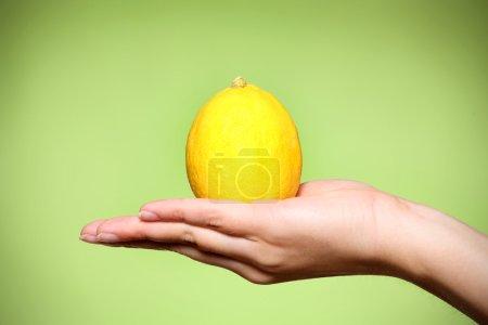 Photo pour Gros plan d'un citron jaune sur fond vert - image libre de droit