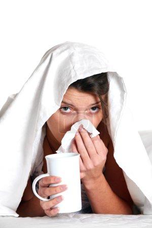 Photo pour Portrait d'une jeune femme au lit avec un froid sur fond blanc - image libre de droit