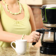 A picture of a young wife preparing coffee in the ...