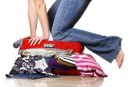 Photo pour Une photo d'une femme ayant des problèmes avec l'emballage d'une valise - image libre de droit