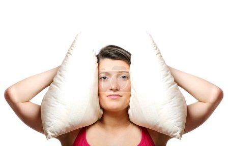 Photo pour Un portrait d'une belle jeune femme couvrant les oreilles avec un oreiller sur fond blanc - image libre de droit