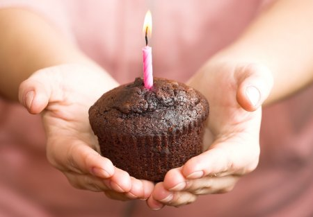 Girl offering you a chocolate muffin with candle