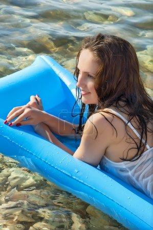 Beautiful woman on a mattress on the sea