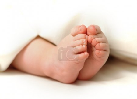 Photo for Uncovered baby boy's small feet - Royalty Free Image
