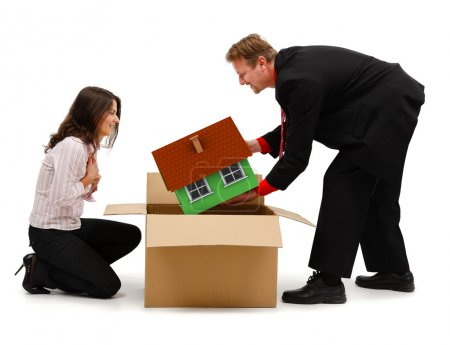 Photo for Business man or husband unpacking a miniature new house for his wife or client - Royalty Free Image