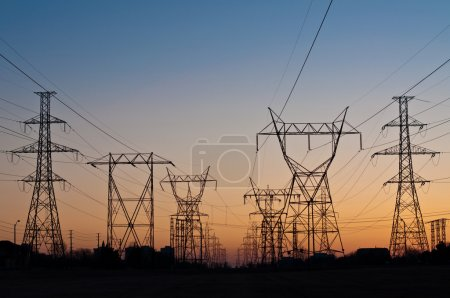 A long line of electrical transmission towers carr...