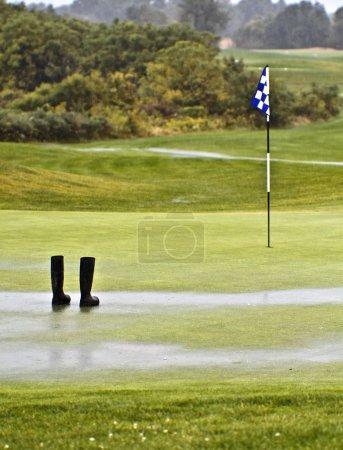 Photo pour Pluie tellement sur le parcours, le jardinier laisse ses bottes sur le vert - image libre de droit