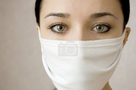 Photo for The face of the beautiful girl (the nurse) with a medical mask protecting it from a flu and other infections. Close up. Beautiful eyes - Royalty Free Image