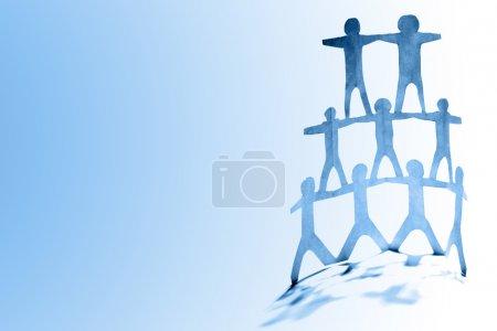Photo pour Pyramide de l'équipe humaine sur fond bleu - image libre de droit