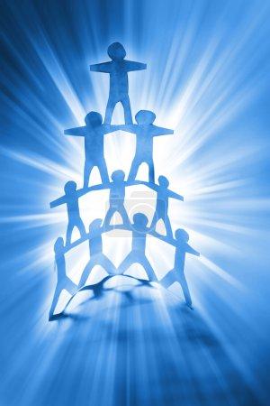 Photo pour Pyramide de l'équipe humaine sur fond bleu vif - image libre de droit