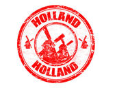Red grunge rubber stamp with windmill silhouette and the name of Holland written inside