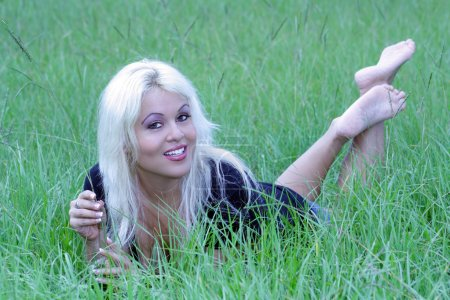 Photo pour Une belle jeune blonde platine avec un sourire lumineux et chaleureux, située dans un terrain gazonné. - image libre de droit