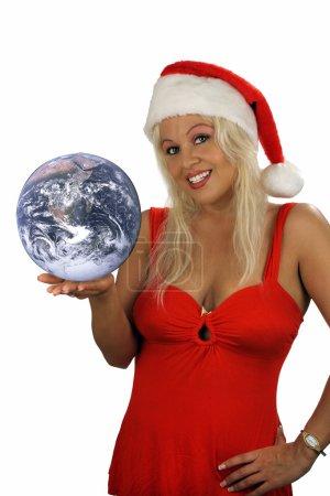 Photo pour Une belle jeune blonde, vêtue de la garde-robe de vacances avec un bonnet de helper, tient la terre dans sa main. - image libre de droit