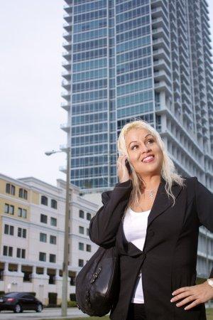 Photo pour Tir faible angle d'une femme d'affaires belle blonde platine parler sur son téléphone cellulaire à l'extérieur avec un immeuble de grande hauteur derrière elle. - image libre de droit