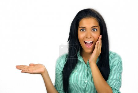 Photo for Close-up of an lovely, excited or surprised teenage Latina with a bright, warm smile and long, luscious black hair, holding her hand out flat, palm up, allowing - Royalty Free Image