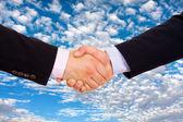 Obchodní muži ruku protřepat nad modrou oblohu s mraky jako poza