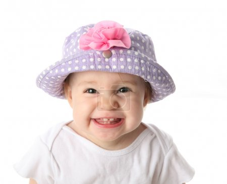 Photo for Smiling baby girl showing teeth wearing a purple polka dot hat with pink flower isolated on white background - Royalty Free Image