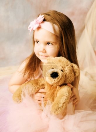 Photo for Adorable little girl dressed as a ballerina in a tutu and bow headband hugging a teddy bear. - Royalty Free Image