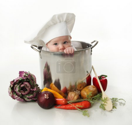 Photo for Portrait of a smiling baby sitting wearing a chef hat sitting inside a large cooking stock pot surrounded by vegetables and food, isolated on white - Royalty Free Image
