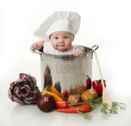 Photo for Portrait of a smiling baby sitting inside a large cooking stock pot surrounded by vegetables and food, isolated on white - Royalty Free Image