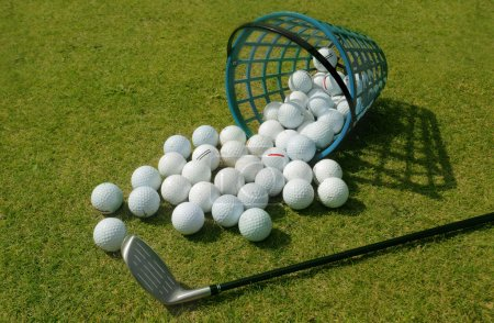 Photo pour Balles de golf coulant du panier sur l'herbe - image libre de droit