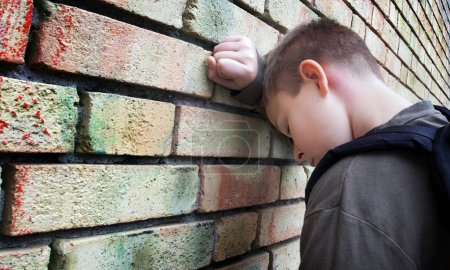 Photo for Upset boy against a wall - Royalty Free Image