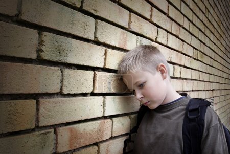 Photo for Upset boy leaning against a wall - Royalty Free Image