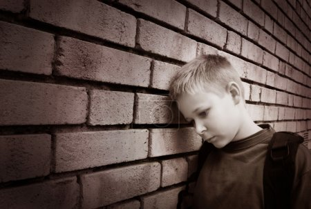 Photo for Black and white picture of an upset boy leaning against a wall - Royalty Free Image