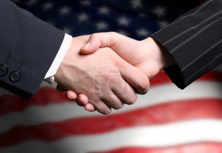 Photo pour Une poignée de main et un drapeau américain - image libre de droit