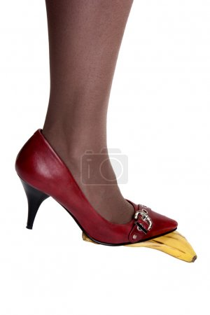Photo for Foot in red pumps on banana peel against a white background - Royalty Free Image