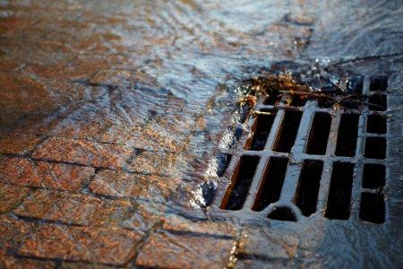 Photo pour Fondu l'eau coule à travers la couverture de trou d'homme sur un jour de printemps ensoleillé - image libre de droit
