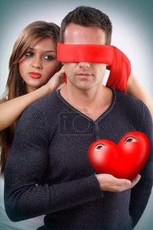 Photo pour Femme bander un homme tenant son coeur yeux ouverts à la main - image libre de droit
