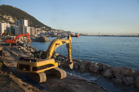 Photo pour Une pelleteuse rouge et jaune travaillant à Gibraltar - image libre de droit