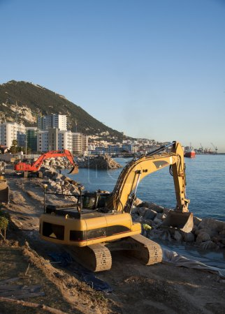 Photo pour Une pelleteuse jaune et rouge, travaillant à gibraltar - image libre de droit