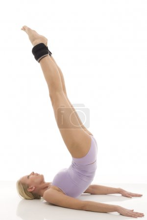 Portrait of a young caucasian woman does gymnastics with ankle weights